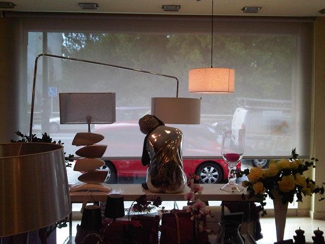 Cortinas enrollables en el interior de una tienda para que con el sol no se estropeen los objetos del escaparate