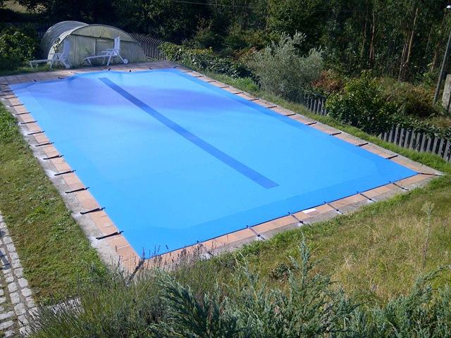 Cubierta para piscina en lona de PVC azul con tacos y mordazas