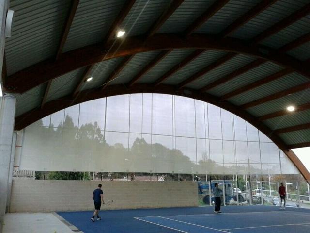Lona perforada que permite pasar la luz natural pero impide que entre el agua y el viento, TGM la ha colocado en las pistas de pádel de Santiago de Compostela