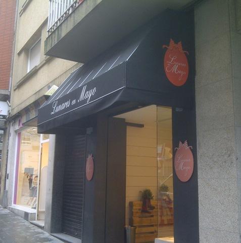 Capota de un negro elegante rotulada en blanco con el logo de la tienda en ambos laterales
