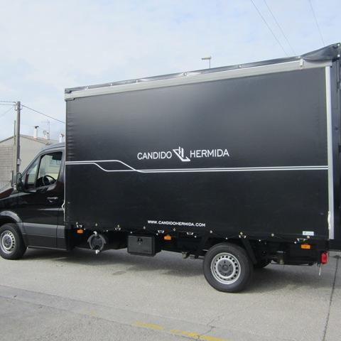 Camión Cándido Hermida luciendo una elegante lona negra rotulada con ollaos y goma elástica para su sujeción